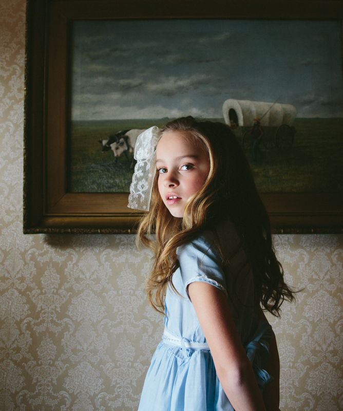 Girl in Vintage Dress in Front of Painting