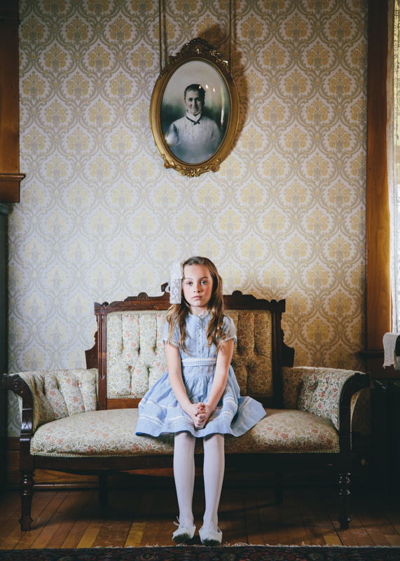 Girl on Antique Sofa with Portrait on Vintage Wallpaper